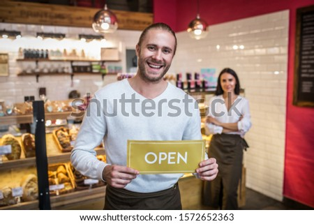Bearded handsome man. Bearded handsome man smiling while opening pastry shop with his wife