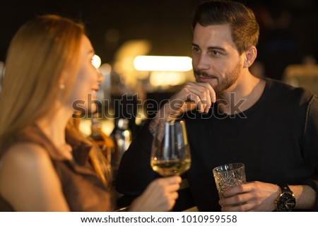 Bearded handsome man smiling thoughtfully listening to his beautiful woman talking while enjoying drinks together at the bar copyspace flirting dating romantic seduction couples communication