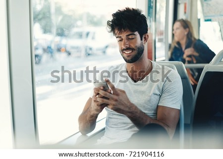 Bearded hipster guy is reading emails on a display of a smartphone connected to public wi-fi while sitting in a city bus. Handsome male is looking at the screen of a mobile phone while texting.