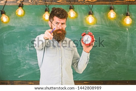 Bearded hipster holds clock, chalkboard on background, copy space.. Teacher in eyeglasses holds alarm clock and pointing forward. Discipline concept. Man with beard and mustache on strict face #1442808989