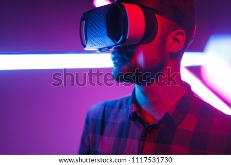 Bearded hipster wearing modern goggles of virtual reality and standing in bright neon lights looking away #1117531730