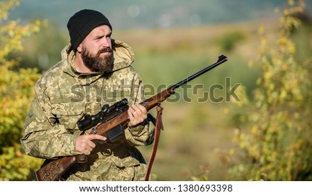 Bearded hunter spend leisure hunting. Focus and concentration of experienced hunter. Regulation of hunting. Hunting masculine hobby concept. Man brutal gamekeeper nature background. Hunter hold rifle.