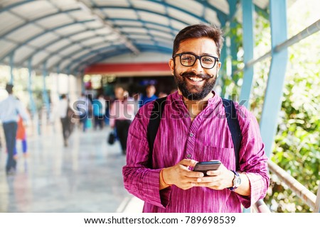 Bearded indian man on metro station using app in his smartphone  #789698539