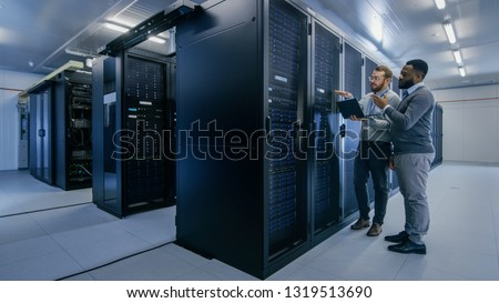 Bearded IT Technician in Glasses with a Laptop Computer and Black Male Engineer Colleague are Talking in Data Center while Working Next to Server Racks. Running Diagnostics or Doing Maintenance Work. #1319513690