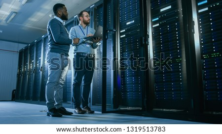 Bearded IT Technician in Glasses with a Laptop Computer and Black Male Engineer Colleague are Talking in Data Center while Working Next to Server Racks. Running Diagnostics or Doing Maintenance Work.