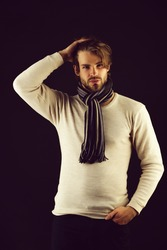 Bearded macho with striped scarf looking confidently, isolated on black background. Concept of assuredness and style