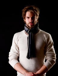 Bearded macho with tied striped scarf looking confidently, isolated on black background. Concept of style and self assuredness
