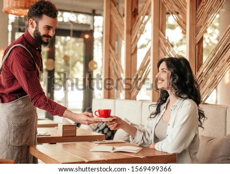 Bearded male barista in apron smiling and giving cup of fresh coffee to female customer while working in cozy cafe