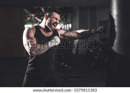 Bearded Male boxer training with punching bag in dark sports hall. Young tattoed boxer training on punching bag. Male boxer as exercise for the big fight. Boxer hits punching bag.