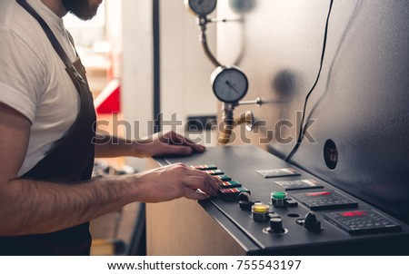 Bearded male master pressing button on special equipment for creating coffee. Technical appliance concept. Close up of his hand #755543197