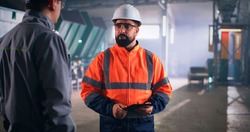 Bearded male supervisor with tablet talking with engineer during inspection in factory workshop