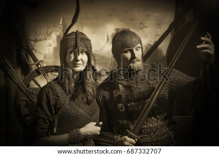 Stock Photo Bearded man and girl in medieval knight costumes with chain mail and swords and bows