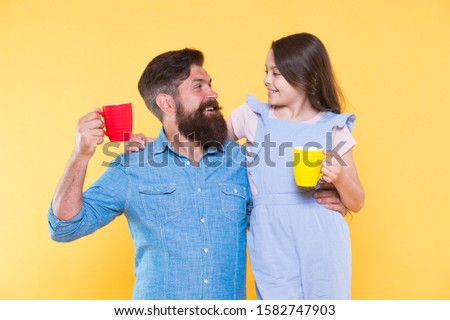 Bearded man and happy girl holding mugs. Father and daughter hot drink. Drink water. Drink fresh juice. Breakfast concept. Good morning. Having coffee together. Healthy lifestyle. Family drinking tea.