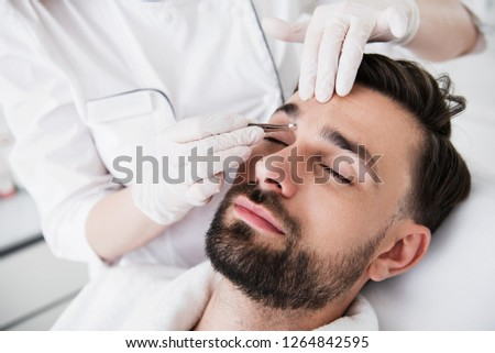 Bearded man closing his eyes at the plucking eyebrows procedure and cosmetologist holding a pair of tweezers at his face