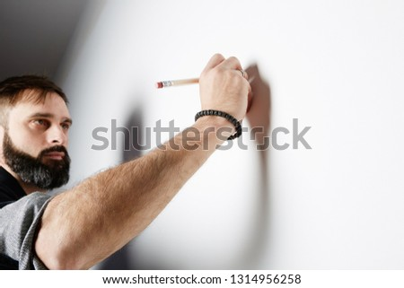 Bearded man drawning on the empty wall background #1314956258