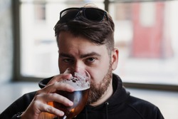 Bearded man drinks beer in a bar and looks at the camera