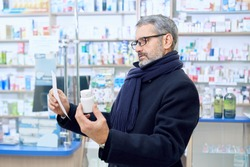 Bearded man frowning, holding white bottle mock and prescription paper in hands. Customer wearing eyeglasses and scarf. Old man reading, choosing medical products in apothecary store.