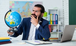 bearded man geographer work in classroom with map. prepare for exam. college lecturer on geography lesson. back to school. informal education. serious mature teacher looking at globe