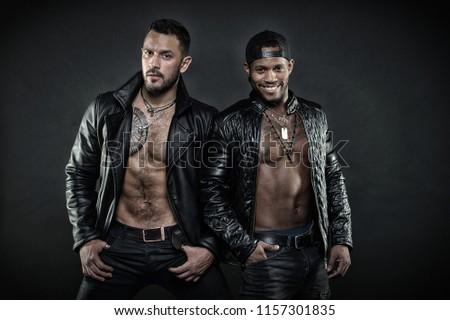 06459b6ef94 Bearded man holding hands in pockets. African man wearing cap backwards.  Two male models