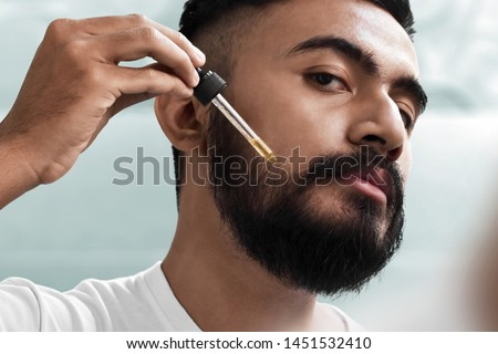 Bearded man holding pippete with beard oil