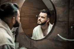 Bearded man in a bathrobe in the bathroom. Groom morning prepare for wedding at the hotel. Fashion photo of a man.
