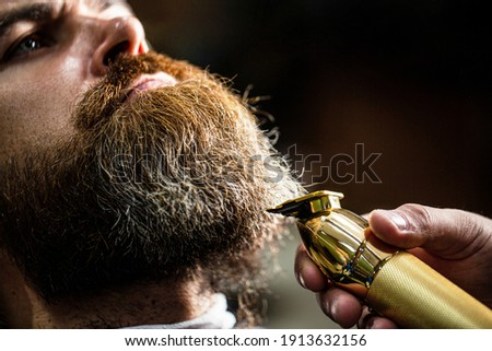 Bearded man in barbershop. Man visiting hairstylist in barbershop. Barber works with a beard clipper. Hipster client getting haircut. Hands of a hairdresser with a beard clipper, closeup.