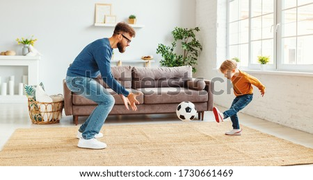 Bearded man in glasses  catching ball while teaching boy to play football in cozy room at home Сток-фото ©