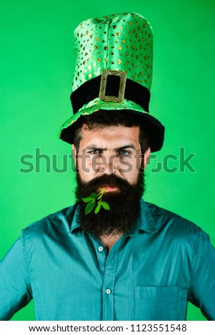 Bearded man in green men hat celebrate Patricks Day. St Patrick's Day Party. Bearded leprechaun with clover in mouth. Saint Patrick. Ireland tradition. Saint Patrick's Day symbols.