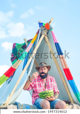 Bearded man in hovel on sky background. Hut of branches. Travel recreational outdoor activity concept. Camping lifestyle. Eco Resort Activities #1497314612