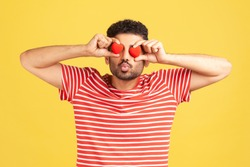 Bearded man in love in red striped t-shirt sending kiss holding toy heart near eyes, love confession, romantic relationships, fondness. Indoor studio shot isolated on yellow background