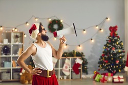 Bearded man in Santa cap and funny holiday costume standing, shouting in speaker and celebrating at home over decorated interior with Christmas tree at background. Christmas and New Year