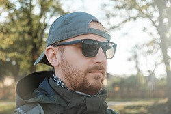 Bearded man in sunglasses and a baseball cap on the background of trees and nature on a sunny autumn day. The concept of a vacation in the countryside, seclusion or hiking.