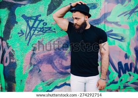 bearded man is a macho, posing near wall with graffiti
