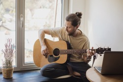 bearded man is sitting at home next to the window and playing the acoustic guitar