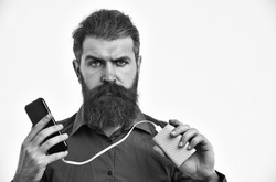bearded man, long beard, brutal caucasian hipster with moustache charging mobile or cell phone with green power bank battery, has serious face, in orange color shirt isolated on white background
