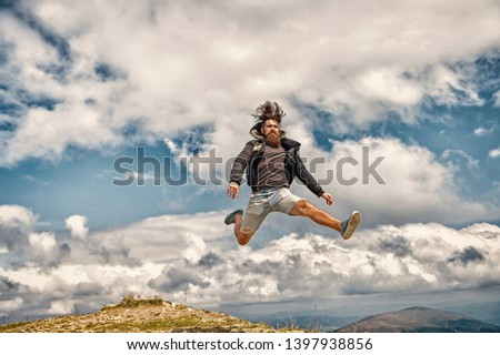 bearded man, long beard, brutal caucasian hipster with moustache jump on sunny mountain top with blue cloudy sky, unshaven guy with stylish hair getting beards haircut on natural background