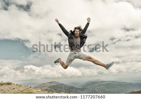 bearded man, long beard, brutal caucasian hipster with moustache jump with happy face on mountain top with cloudy sky, unshaven guy with stylish hair getting beards haircut on natural background