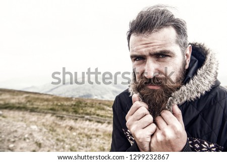bearded man, long beard, brutal caucasian hipster with moustache on serious face, unshaven guy with stylish hair getting beards haircut cower from cold on mountain top on cloudy sky, copy space