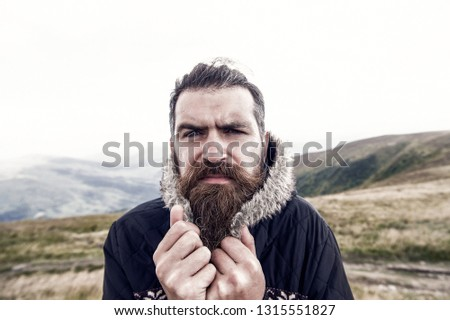 bearded man, long beard, brutal caucasian hipster with moustache on serious face, unshaven guy with stylish hair getting beards haircut cower from cold on mountain top on natural cloudy sky background