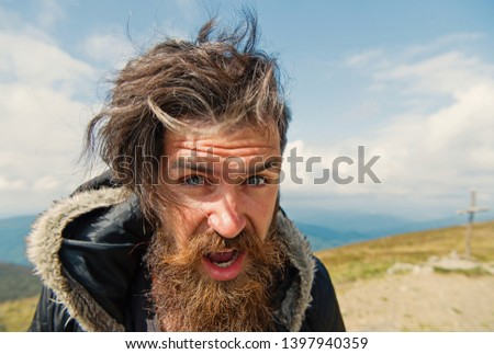 bearded man, long beard, brutal caucasian hipster with moustache on surprised face, unshaven guy with stylish hair getting beards haircut on windy mountain top on natural cloudy sky, copy space