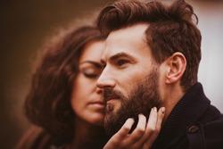 Bearded man looks far away while lovely brunette strokes his face