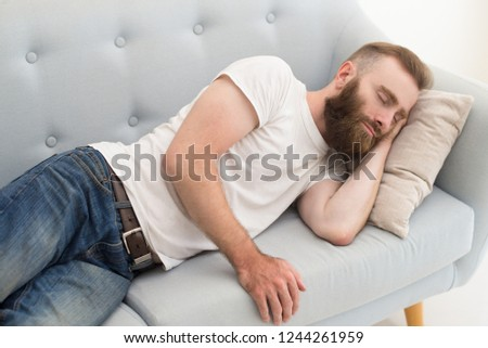 Bearded man lying and dosing on sofa. Handsome guy dozing. Relaxation concept.