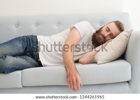 Bearded man lying and sleeping on sofa. Handsome guy dozing. Rest concept. Front view.