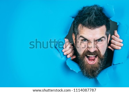 Bearded man making hole in paper. View of angry male face through hole in blue paper. Angry man looking through hole. Bearded man in paper. Isolated. Close up. Emotions.