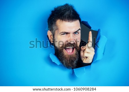 Bearded man making hole in paper. View of male face through hole in blue paper. Bearded man looking through hole and show the finger. Bearded man making hole in paper and points up.