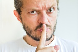 Bearded man making silence gesture, pst, shh, mean expression!