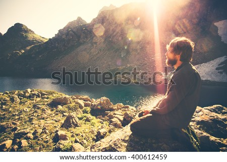Bearded Man meditating relaxing alone Travel healthy Lifestyle concept lake and mountains sunny landscape on background outdoor