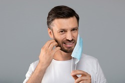 Bearded man moved protective medical mask from face to scratch beard, grey studio background, free space. Do not touch your face, avoid touching your face during pandemic, stay safe during lockdown