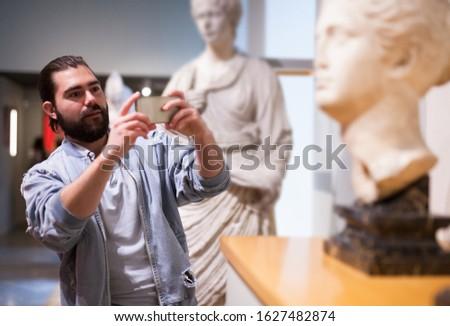 Bearded man photographs museum exhibits using smartphone