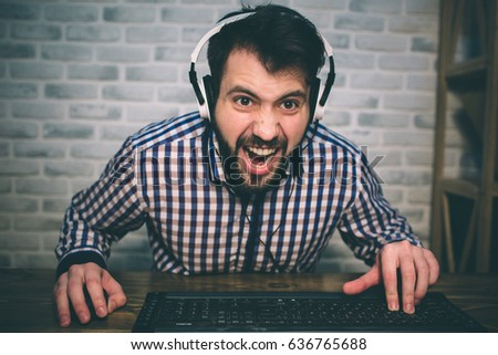 Bearded man playing at home and streaming. Funny guy is excited because of seen virtual video. He is wearing red headphones. #636765688